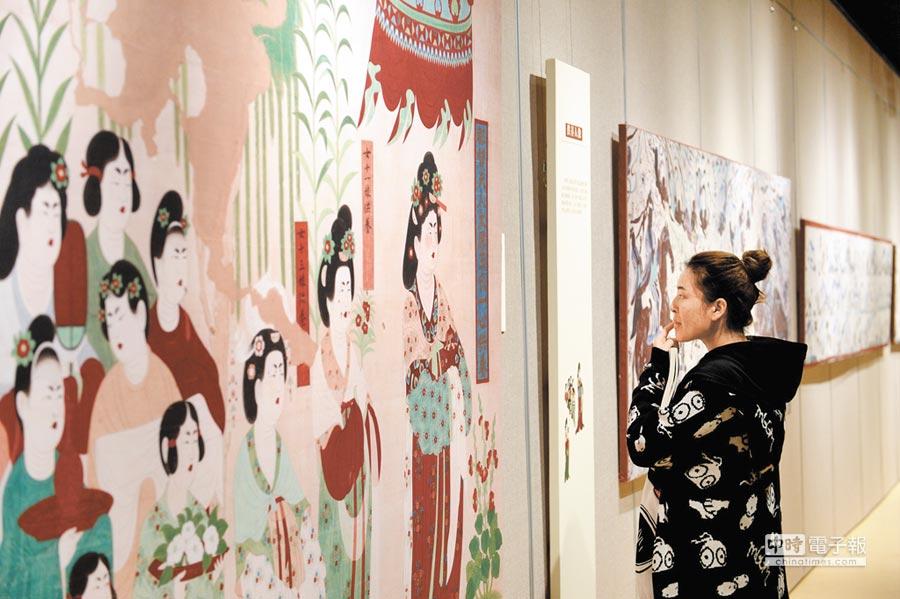 10月14日,一名西北大學學生觀看敦煌文化藝術展上的展品。(新華社)