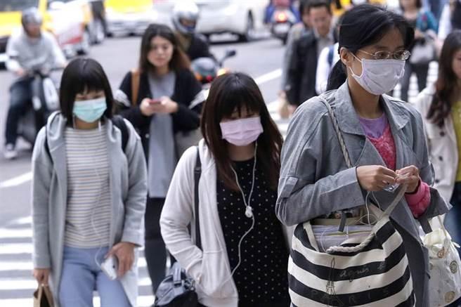 受中國境外污染物影響,街上不少民眾戴口罩上班。(方濬哲攝)