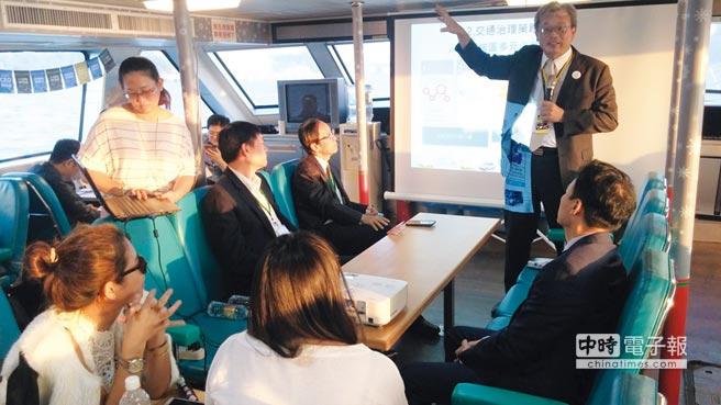 高雄市政府交通局局長陳勁甫(著西裝站立者)於觀光郵輪真愛號上,向高軟CEO聯誼與會貴賓發表演講。圖/加工處提供