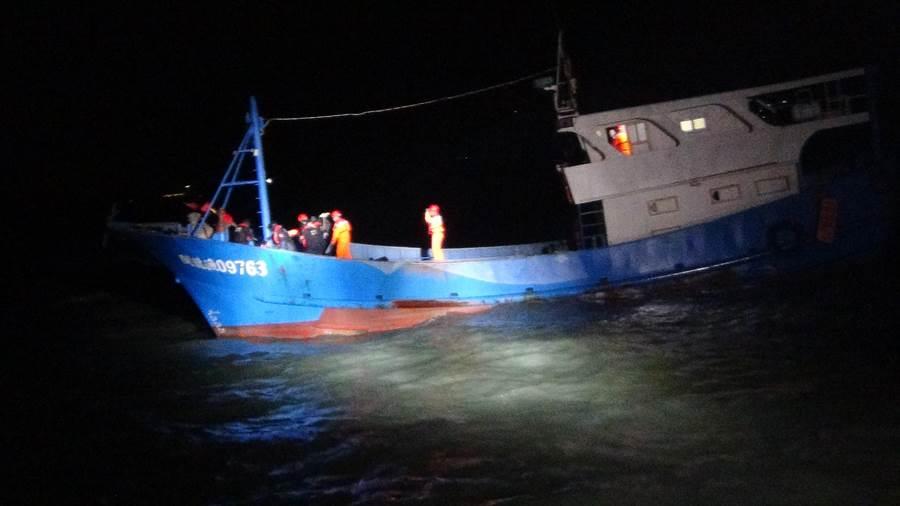 大陸漁船「閩龍漁09763號」越界搶魚,海巡幹員冒著惡劣海象登船取締。(金門海巡隊提供)