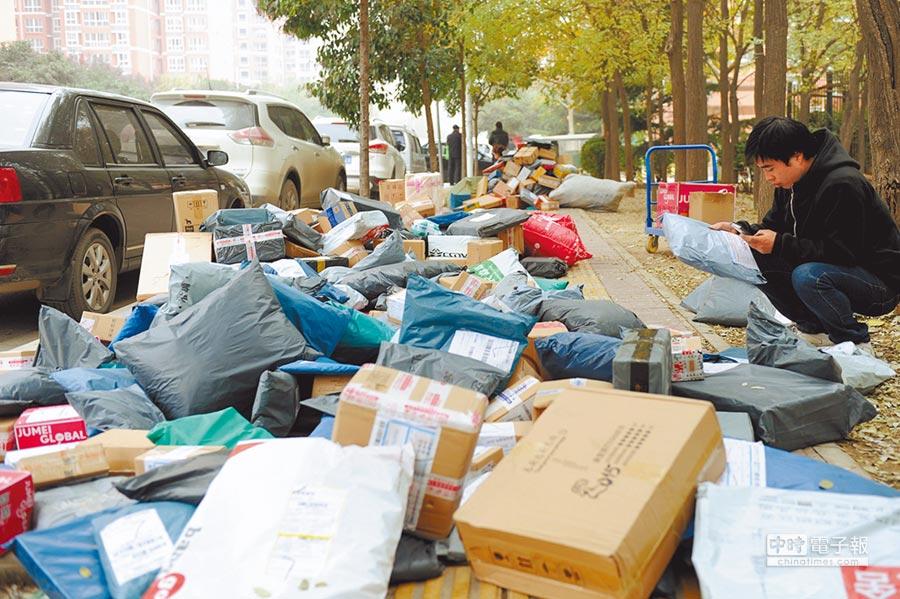 大陆双11后迎来快递业高峰。图为陕西中医大学校园外,近千个快递包裹堆满人行道。(中新社)