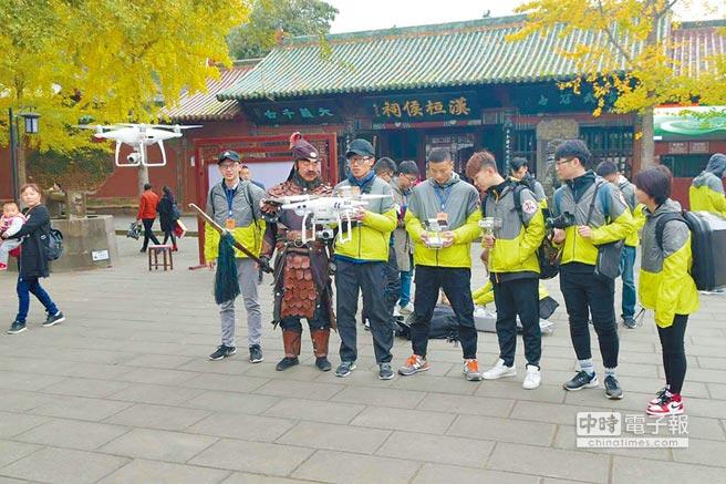 川台大學生24日前往四川閬中,參訪張飛廟,並試飛無人機,還邀請裝扮張飛的演員合影。(記者李侑珊攝)
