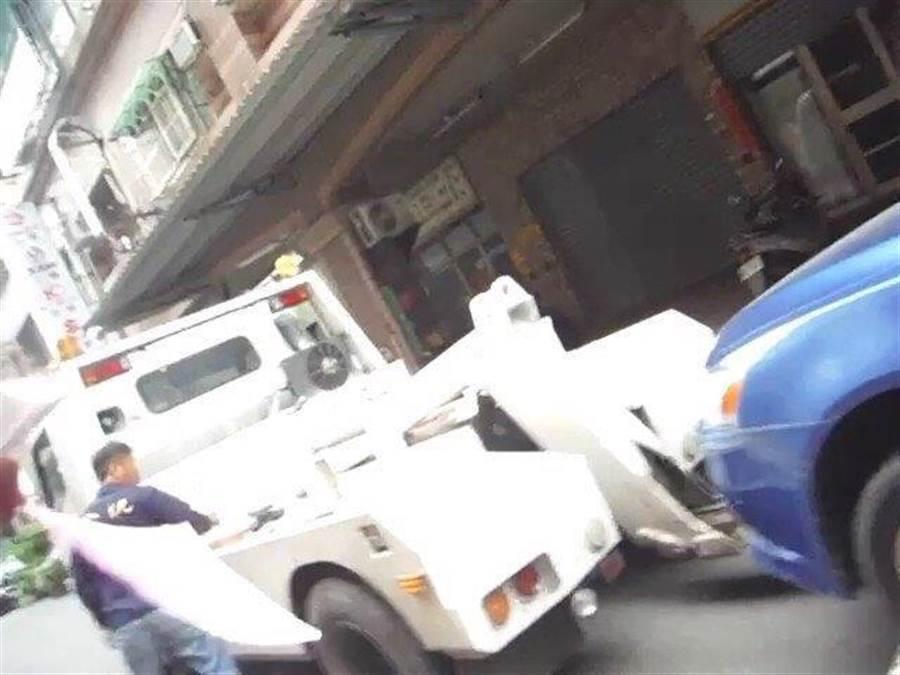 藍色自小客車違規紅線停車,拖吊隊取締執行拖吊。(曹明正翻攝)