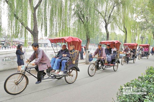 外國遊客乘坐後海八爺三輪車,在北京什剎海景區遊覽。(中新社資料照片)