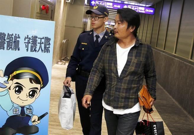 在華航班機上喝酒鬧事的日籍旅客,下機後被航警帶回處理。(范揚光攝)