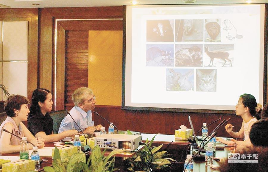 2003年8月15日﹐中外專家在深圳市疾病預防控制中心,了解果子狸等動物有SARS病毒的資料。(新華社)