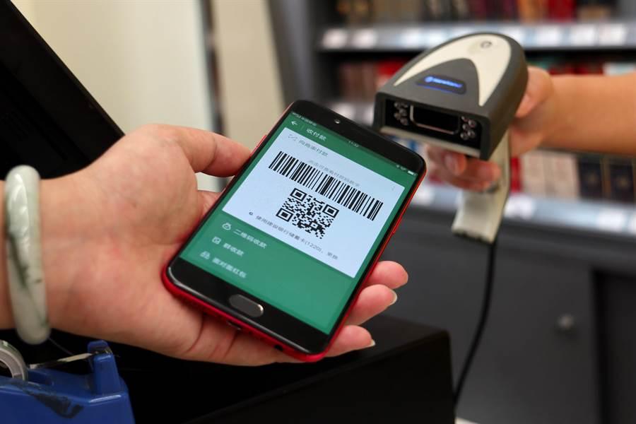 今年中國大陸銀行業手機支付依然大幅成長,首季交易數達93億筆,交易金額達台幣280兆。圖為成都市便利商店內消費者使用手機二維碼支付購物。(圖/中新社)