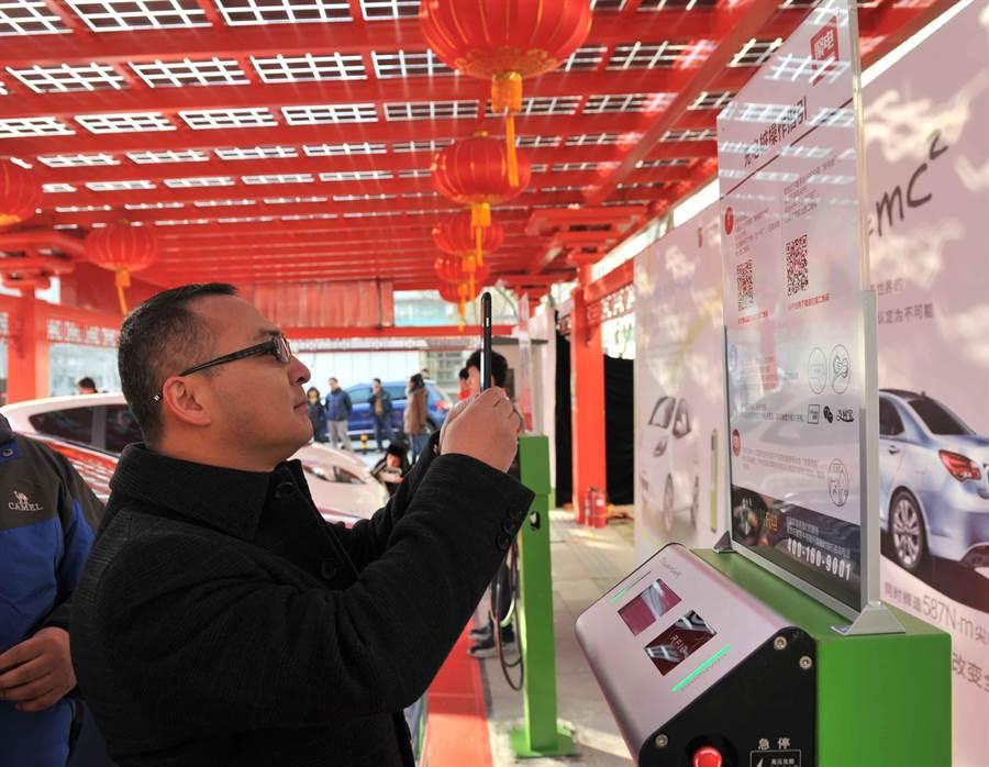 大陸手機支付風行,都市城鎮生活中隨處可見。圖為北京電動汽車公共充電設施,提供消費者以手機掃描二維碼進行支付。(圖/新華社)