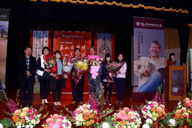 王萬富獲玉山文學貢獻獎表揚,由女兒即親友團代領並獻花。(沈揮勝攝)