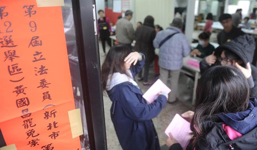 雖然天氣不好飄著細雨,仍有不少民眾帶投票通知單到場,投下神聖一票。(季志翔攝)