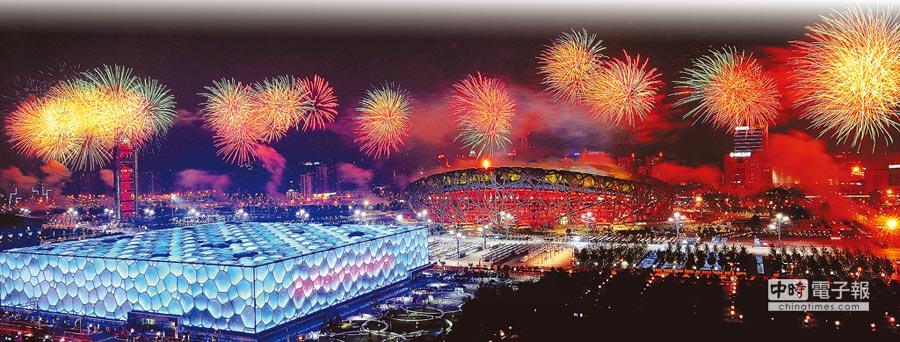 2008年8月24日,北京奧運會閉幕式上,煙火映照的鳥巢和水立方。(新華社)