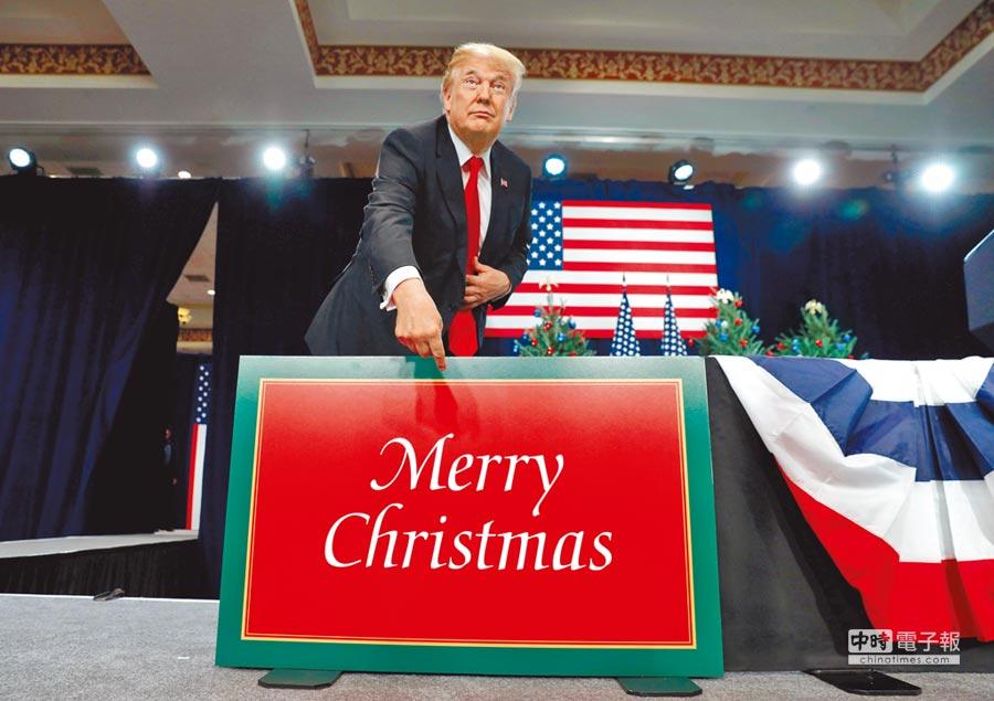川普送出耶誕大禮兌現競選諾言,圖為川普在今年11月29日於密蘇里州聖路易市向當地民眾發表關於稅改方案的演說前,刻意手指著大型的耶誕快樂卡片。(路透)