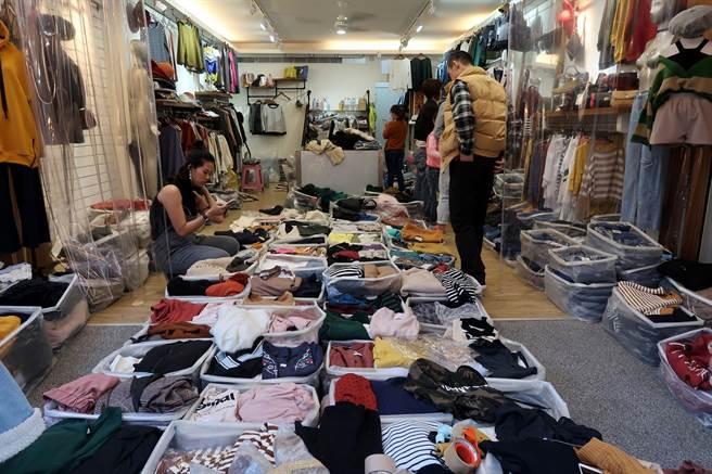 高雄市三民區後驛商圈安寧街是南部最大成衣批發街,有「南部五分埔」之稱,店內一藍一藍的成衣擺放地上,與一般服飾店不同。(呂素麗攝)
