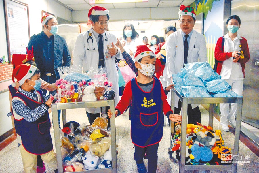 長庚醫護人員將募來的二手玩具仔細包裝成禮物袋,推到兒科病房分送。(李義攝)