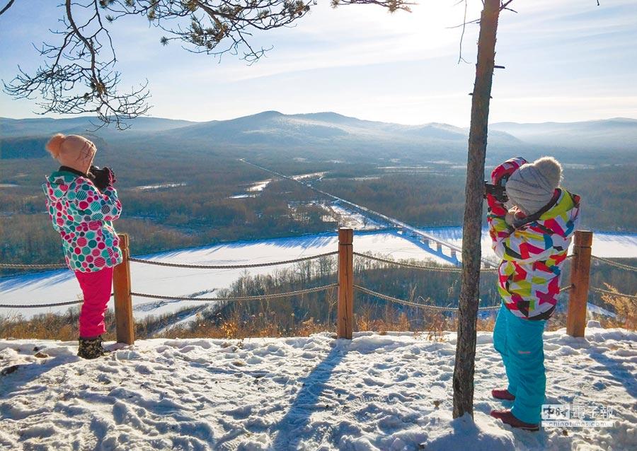 大陸自1月1日起有多項新規上路,包括導遊不得擅自變更行程、強迫遊客購物。圖為2017年12月22日,遊客在位於內蒙古呼倫貝爾伊克薩瑪國家森林公園內拍照。(新華社)