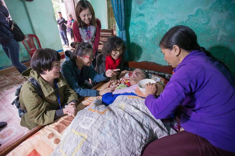 藝人苗可麗(左起)、林嘉俐與陳淑麗看著躺在床上的阿福,雖無法用言語溝通,憑藉笑容傳遞愛心也就足夠了。(圖/至善基金會提供)