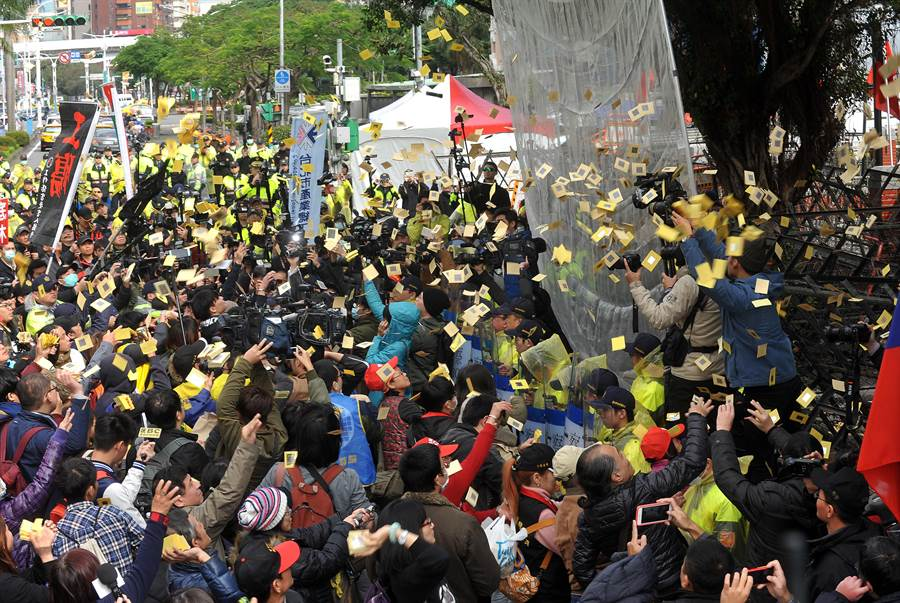 立法院三讀通過勞基法修正案,場外抗議的勞團成員繞行立法院撒冥紙,表達不滿。(劉宗龍攝)