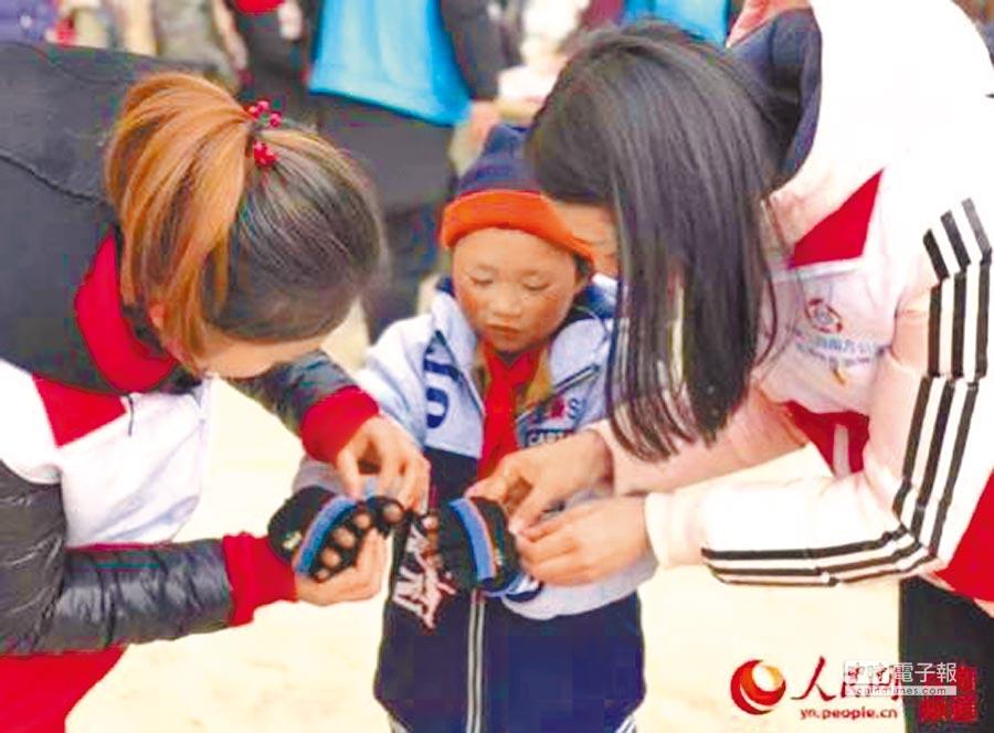 1月10日,中建三局志工在云南转山包小学为王福满穿上棉衣、戴上手套。(取自人民网)