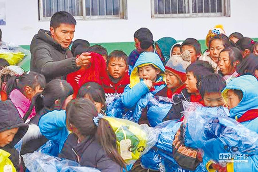 云南转山包小学校长付恒,给孩子发放爱心衣物。(取自澎湃网)