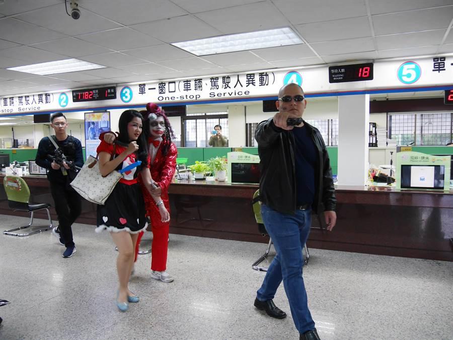 桃園警分局偵查隊員巧扮小丑、港匪和光頭佬,挾持人執行搶監理站,逼真演技吸引民眾圍觀拍照。(蔡依珍攝)