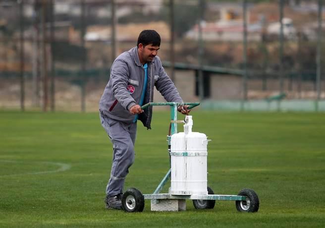 球場工作人員用油漆畫線,讓訓練與比賽能夠順利進行。(李弘斌攝)