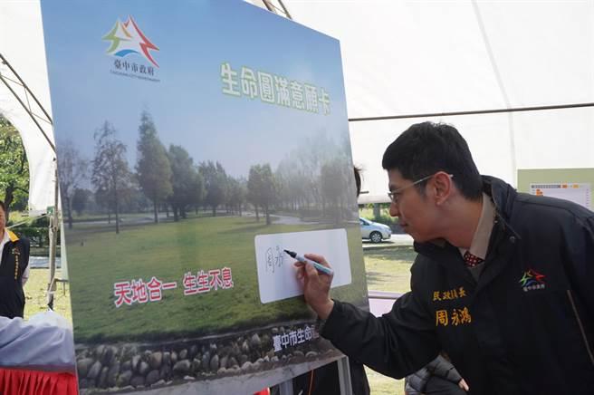 台中市民政局長周永鴻在推廣記者會現場簽署「生命圓滿意願卡」,預立環保葬意願。(王文吉攝)