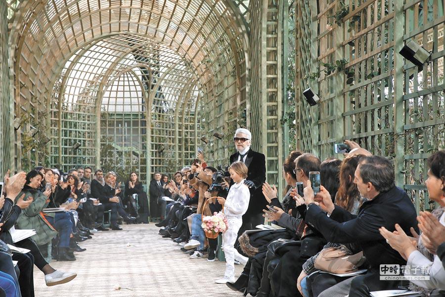 滿臉白鬍造型的老佛爺,在小花童Hudson Korenig的引領下,與身著白紗的模特一同謝幕。(CFP)