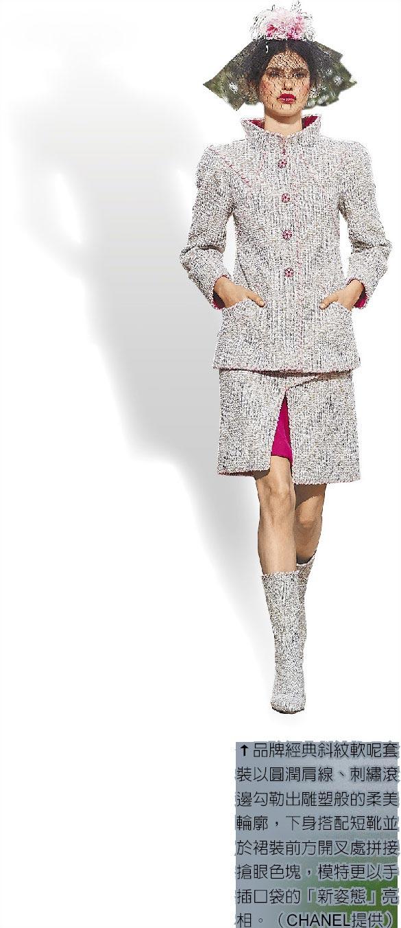 品牌經典斜紋軟呢套裝以圓潤肩線、刺繡滾邊勾勒出雕塑般的柔美輪廓,下身搭配短靴並於裙裝前方開叉處拼接搶眼色塊,模特更以手插口袋的「新姿態」亮相。(CHANEL提供)