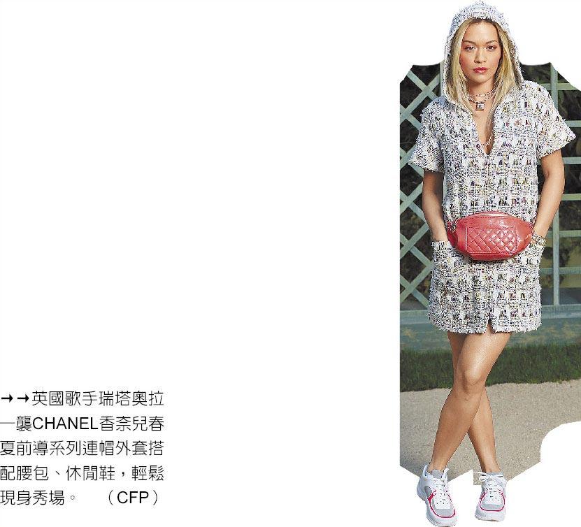 英國歌手瑞塔奧拉一襲CHANEL香奈兒春夏前導系列連帽外套搭配腰包、休閒鞋,輕鬆現身秀場。(CFP)