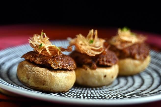 〈臘腸鑲蘑菇〉是將西班牙臘腸切末,與洋蔥、乾蔥一起鑲入大朵多汁的蘑菇,並在上方搭配烤至酥脆的伊比利火腿,造型討喜,每份165元。(圖/姚舜攝)