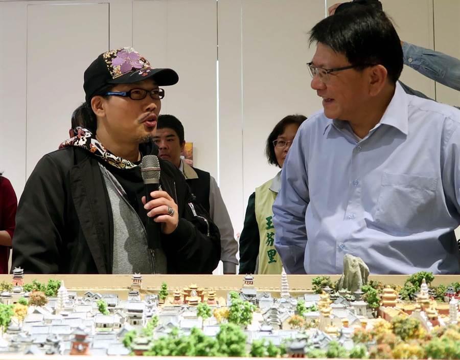 屏東美術館展出華語歌壇知名作詞人方文山(左)作品「精靈小屋.微型村莊」,並向屏東縣長潘孟安(右)說明創作理念。(潘建志攝)