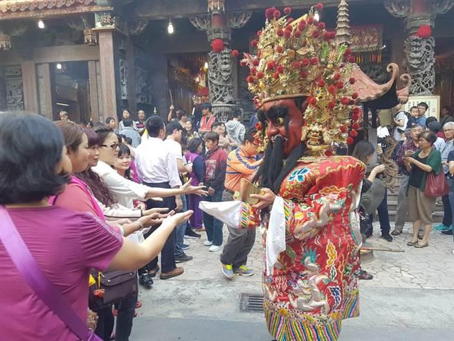 財神爺廟前廣場撒糖果給民眾「吃甜甜」活動,接著拿紅包福袋逐一發送,民眾爭相搶拿。(張妍溱攝)