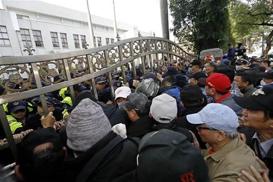 反年改團體27日清晨突襲立法院,與警方數度發生衝突,抗議群眾情緒激動,數度推擠鐵門,更有人爬上圍牆,意圖翻入立院。(張鎧乙攝)