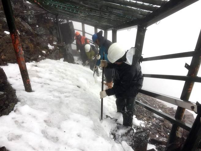玉管處保育巡查員上山清理步道殘雪,但因結冰,不少路段仍相當溼滑。(玉山國家公園管理處提供)