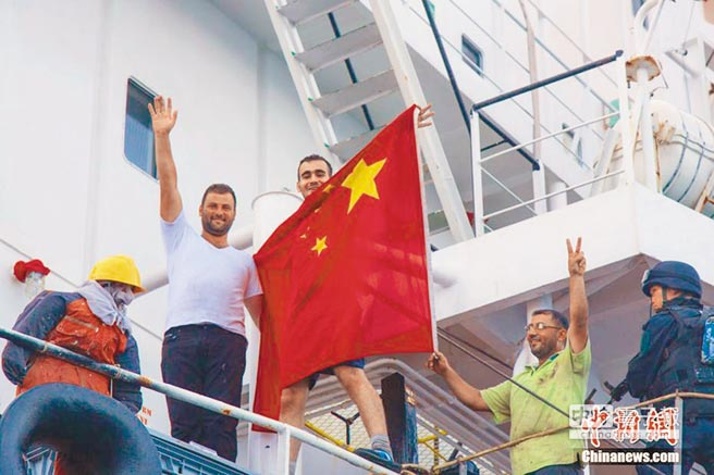 被中國海軍解救的外國船員舉著五星旗以示感謝。(取自中新網)