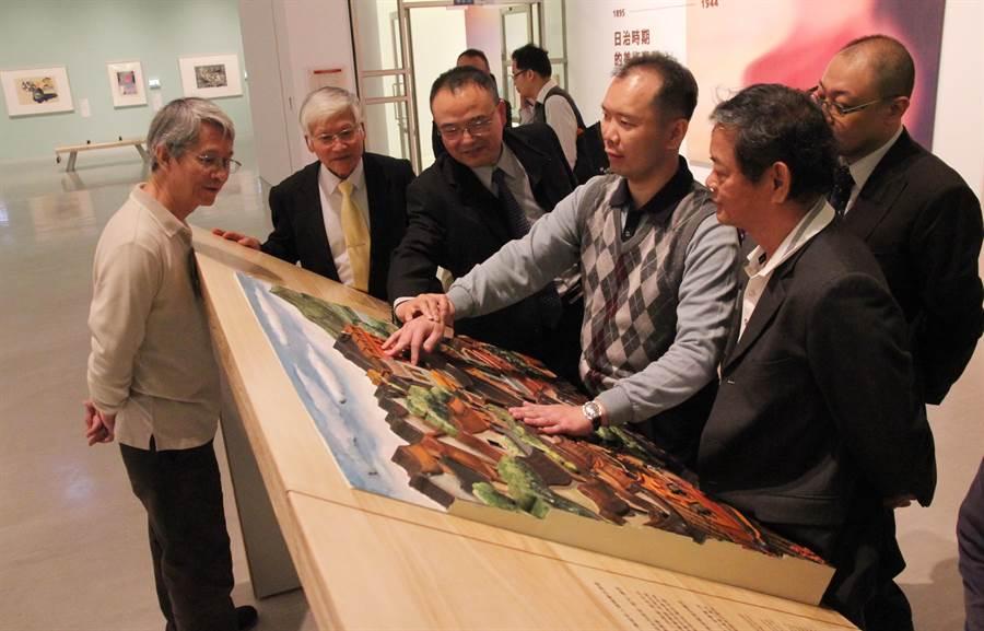 國美館館長蕭宗煌(左3)引導清華大學特殊教育系副教授黃國晏(左4)觸摸《淡水風景》3D觸摸輔具版,用觸感來體驗大師名畫。(陳淑芬攝)
