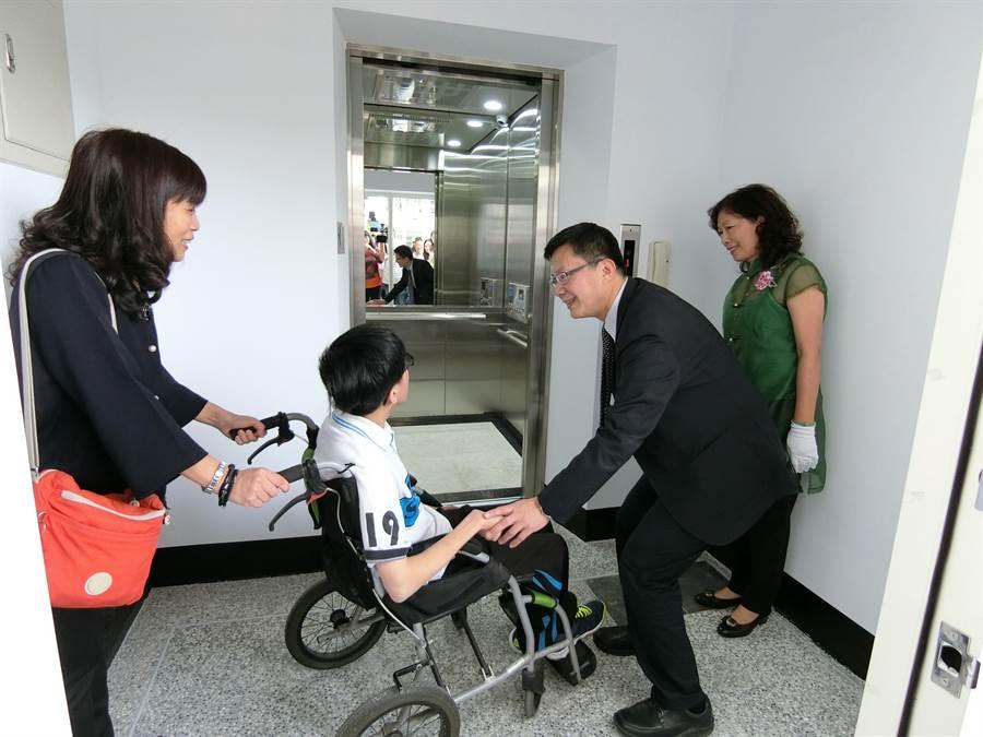 劉柏岑(左二)坐輪椅,靠著電梯設備,不需別人協助,也能方便上下樓。(盧金足攝)