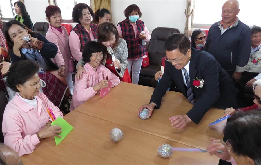 童心未泯的魏明谷,將紙製的桌球當成骰子丟,逗老人家開心。(鐘武達攝)