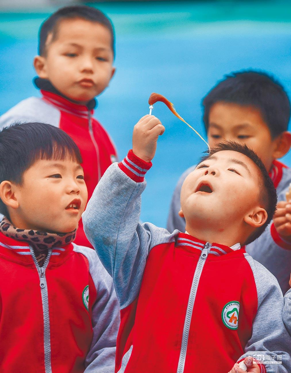 麥芽糖具有生津潤燥功效。圖為孩子們品嘗麥芽糖。(新華社)