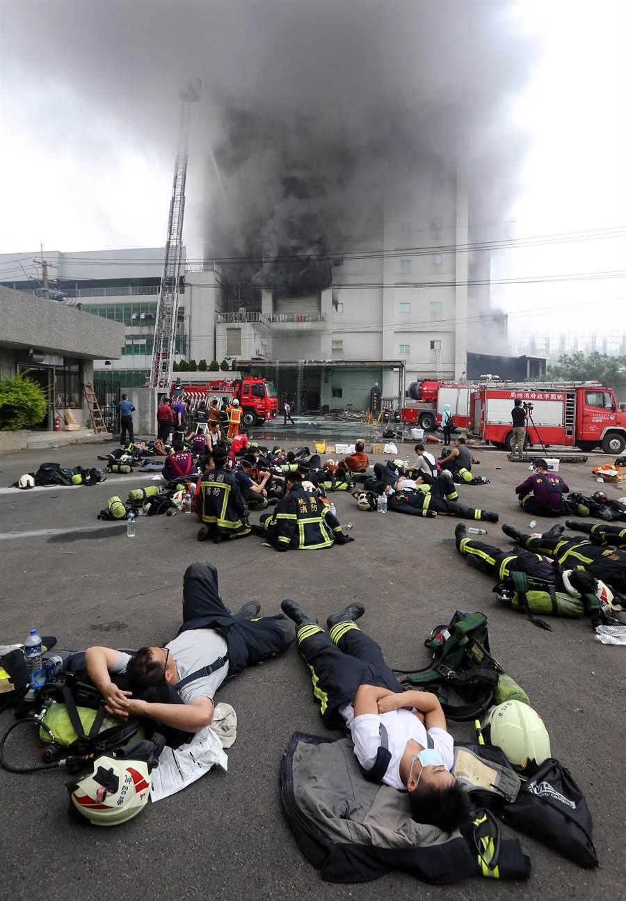 敬鵬工業公司平鎮廠28日晚間發生大火,由於火勢延燒到29日,徹夜未眠的打火弟兄累得就地躺平。(范揚光攝)