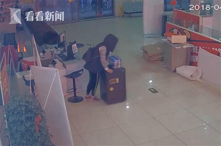 女子套上連衣帽遮掩面目後將保險櫃推走