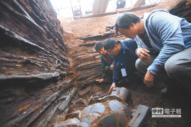 2011年11月22日,遼寧發現大型戰國古墓,考古工作人員在研究出土的彩陶。(新華社)