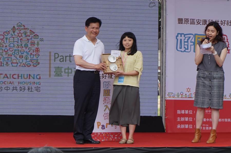 台中市長林佳龍(左)致贈碗筷紀念品給住戶代表劉宛諭,祝福住戶「喜樂安康」。(王文吉攝)