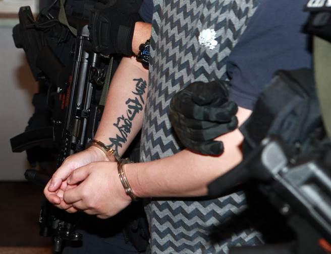 2嫌的右手上還都有相同的「隻守遮天」刺青,但仍逃不過法網,警方於10日晚間將2人押解回台。(陳麒全攝)