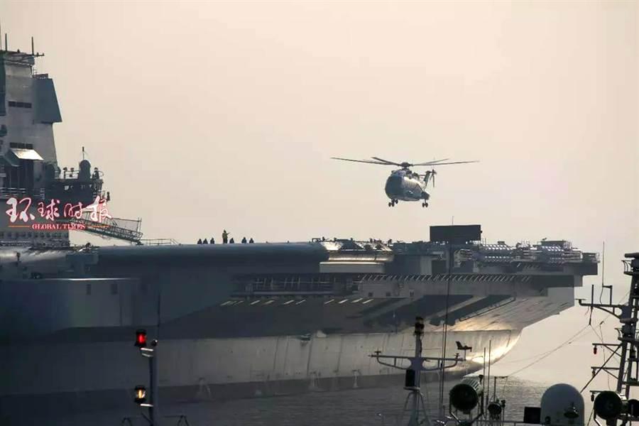 共軍直-18運輸直升機在大陸國產航母甲板上降落,目前這艘航母正在大連港附近海域試航。(圖/環球時報)