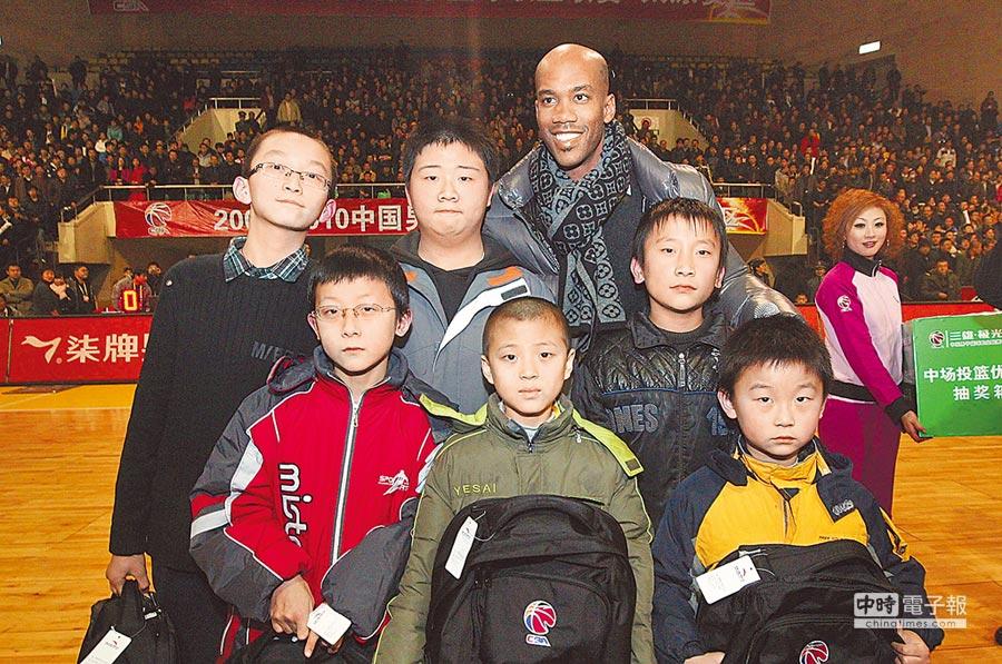 NBA前球星史蒂芬.馬布里2010年到大陸打職籃,現定居北京。圖為馬布里(後)與大陸小球迷合影。(中新社資料照片)