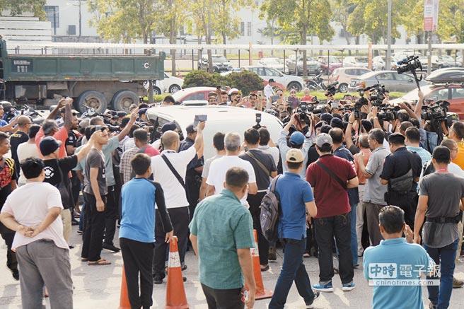 聽聞前首相納吉布夫婦可能搭機出逃,大批民眾12日前往機場附近圍堵,每有車輛接近,大群人便一擁而上。(法新社)