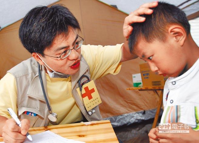 2008年5月21日,台灣紅十字醫療隊在四川高坪鎮災民安置中心展開救治。外科醫生李俊秀(左)為10歲男童黃世文診病並開導安慰他。(中新社)