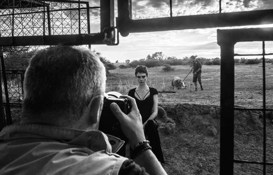 導演David Yarrow躲在籠子內拍攝卡拉與獅子合影畫面。( TAG Heuer提供)