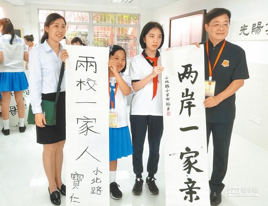 兩岸姐妹校舉行交流活動,學生展示書法「兩校一家人,兩岸一家親」。(中新社)
